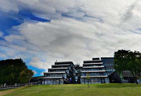 Exterior of glass terraced Checkland building against dramatic summer clouds, Falmer Campus