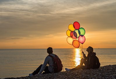 Two people on Brighton beach at sunset with balloons
