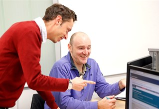 MBA students looking at a computer screen