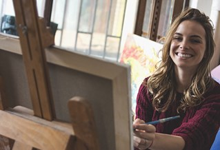 Smiling woman working at easel