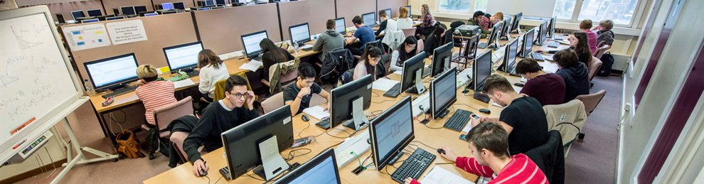 Three rows of desks with students working at computers