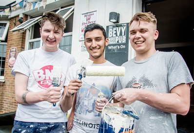 Three student volunteers with paintbrushes outside the Bevy community pub