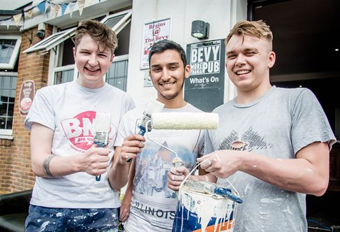 Three students volunteers with paint and rollers outside the Bevy pub