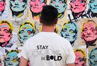 Stay Curious student looking at poster art