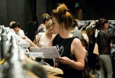 Young woman looking through racks of clothes at a fashion show
