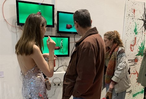Fine Art student and visitors look at video screens.jpeg
