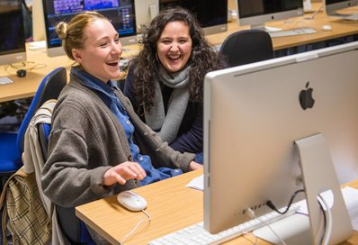 Students laughing in front of the computer