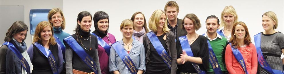 A line of masters students all wearing blue sashes