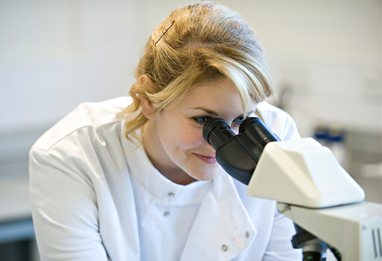 Pharmacy student looking through microscope