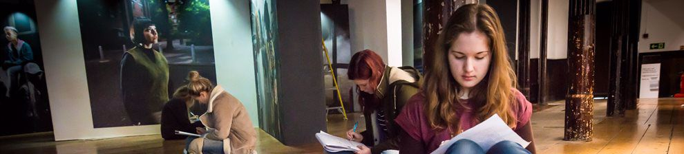 Students making notes in a photography gallery