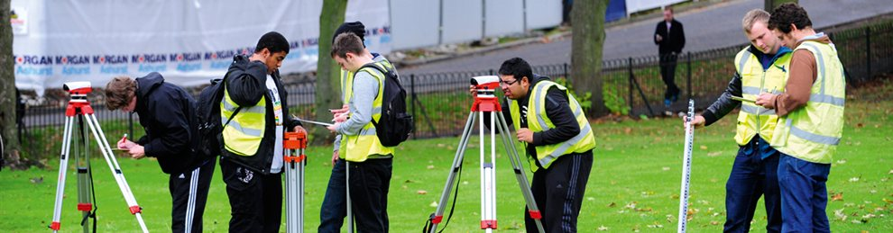 Students using equipment to survey a field