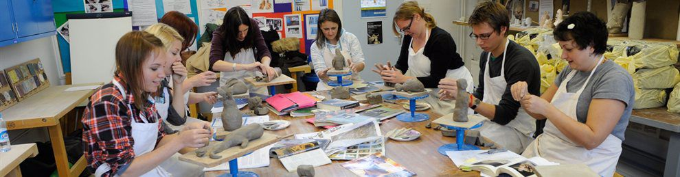 Photo of students relaxing in a pottery class.