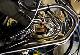 Photograph of engine pipes with researcher in background