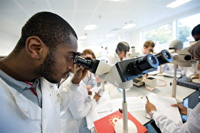 Student in a white coat looking into a microscope