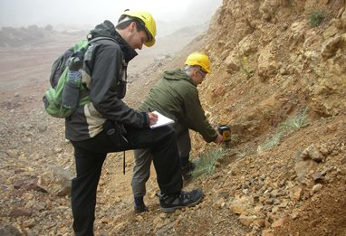Two geologists in hard hats analysing the soil