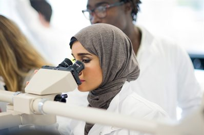 A student in a white coat looking into a microscope
