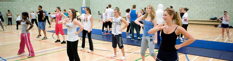 Students having an exercise session in a gym hall.