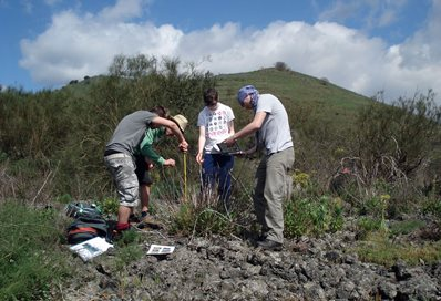 Four students analysing the rocky soil at the base of a hill