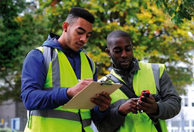 Two students in hi-viz comparing readings outside