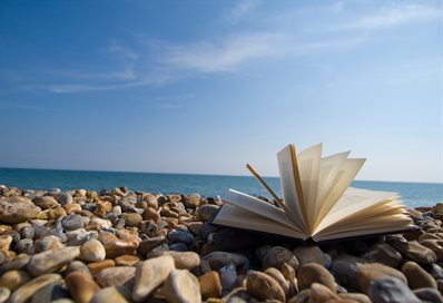 An open book on a pebble beach with the sea and sky in the background