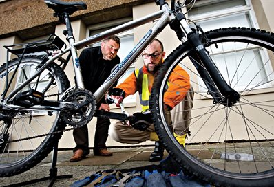 Dr Bike looking at a bicycle, with owner watching