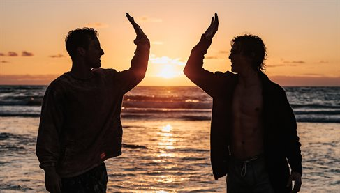 Silouette of two men 'high-fiving' near the seashore at sunset. Credit: Tyler Nix / Unsplash