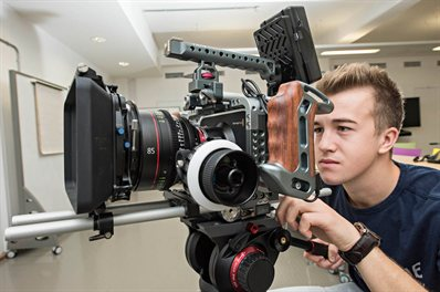 A student peering into the viewfinder of a film camera in a studio