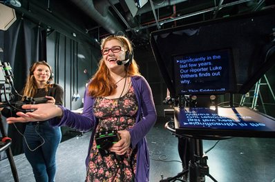 Two students in a studio with a teleprompter