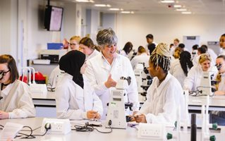 Biomedical science students in white coats in a teaching laboratory