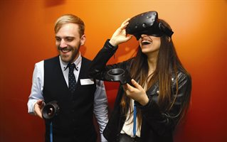 Two students with a VR headset at a Computing degree show