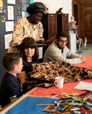 A mixed age group in a museum setting share stories of black and ethnic minority origins using cloth and textile props and writing materials