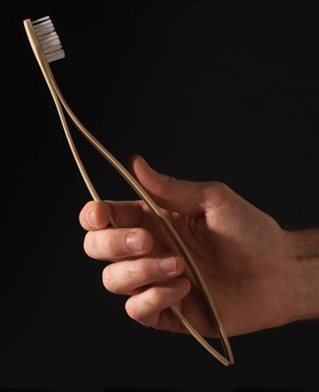 Hand gripping toothbrush designed with two flexible handles designed to be squeezed as help for rheumatoid arthritis sufferers