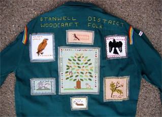 Dark blue shirt with Stanwell District Woodcraft Folk sewn on and various animal and nature badges