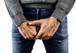 Image of a man with his hands over his groin area