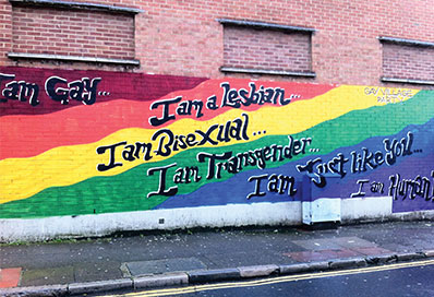 Painted street wall art in rainbow colours with words I am Gay I am a lesbian Iam Bisexual I am Transgender I am Just like you....