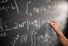 photograph of someone writing mathematical formulae on a blackboard