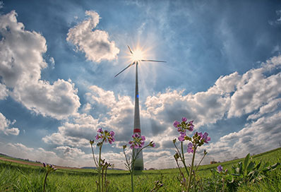 Wide angle lens view of clouded sky and field with tall electricity generating windmill