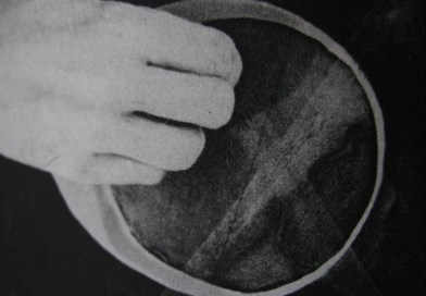 Black & white image of a hand holding a vessel