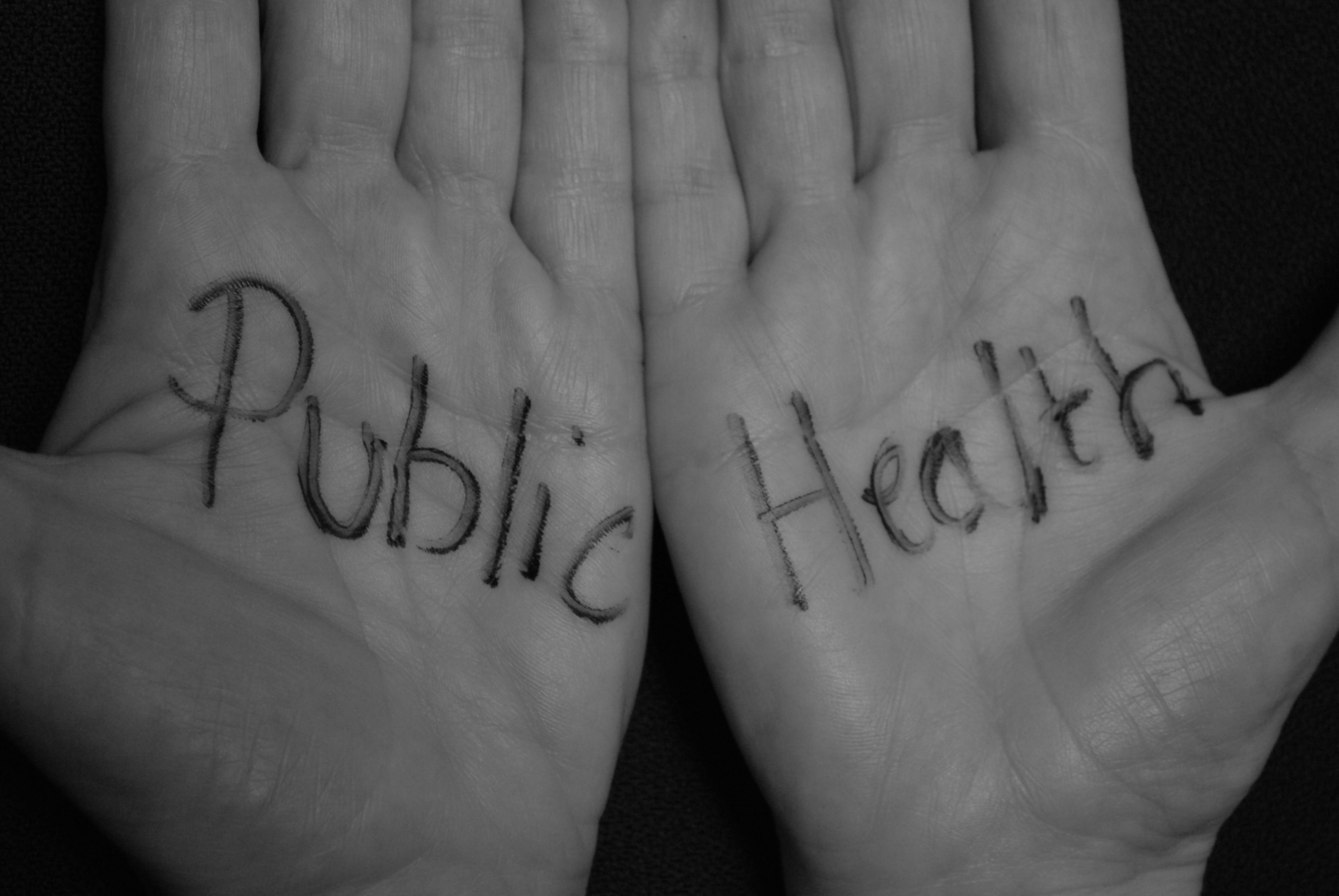 Words public health written across two palms to illustrate Public Health and Wellbeing REG image