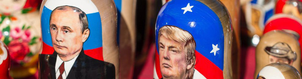 Close up of two Russian dolls, one depicting Vladimir Putin, the other Donald Trump.