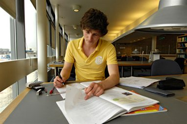 A student in front of some books in a university library