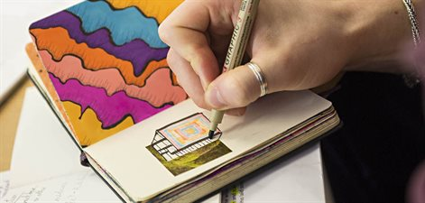 Drawing colourful shapes in a notebook