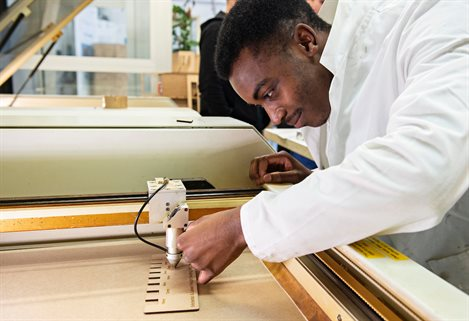 male student working with the laser cutter