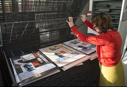 A woman looking through racks of prints
