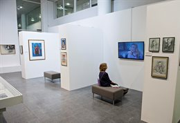 Student sitting in front of pictures at a university gallery
