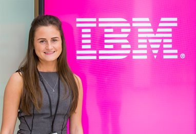 Placement student in front of IBM logo