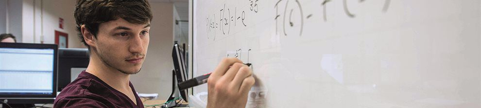 Maths student working on whiteboard