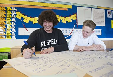 Two students writing on large pieces of paper from a flip chart