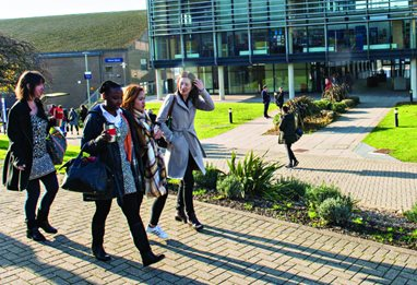 Four students walking in front of the Checkland Building at Falmer, casting long shadows