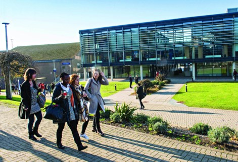 Group of students walking past Checkland Bulding on Falmer campus